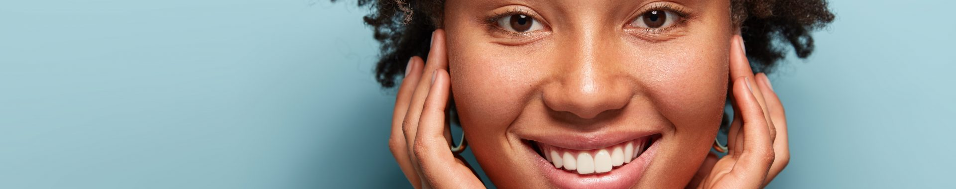 banner for face and skin treatments featuring a smiling black woman with beautiful, healthy skin