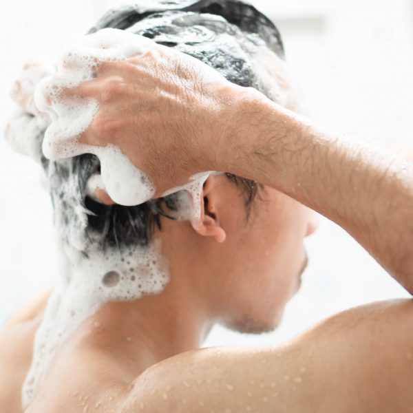 man shampooing worried about hair loss