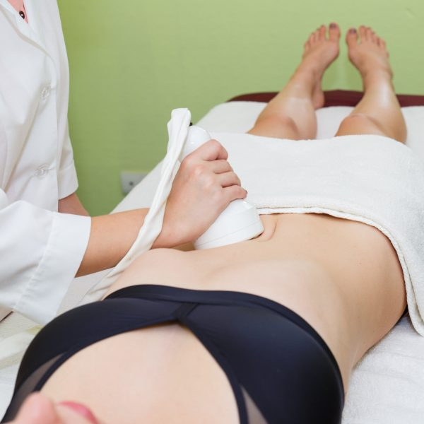 A woman has ultrasound cavitation treatment on her stomach in a clinic