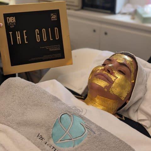 woman has the DIBI 24-Karat Gold Leaf Facial at Vie Aesthetics